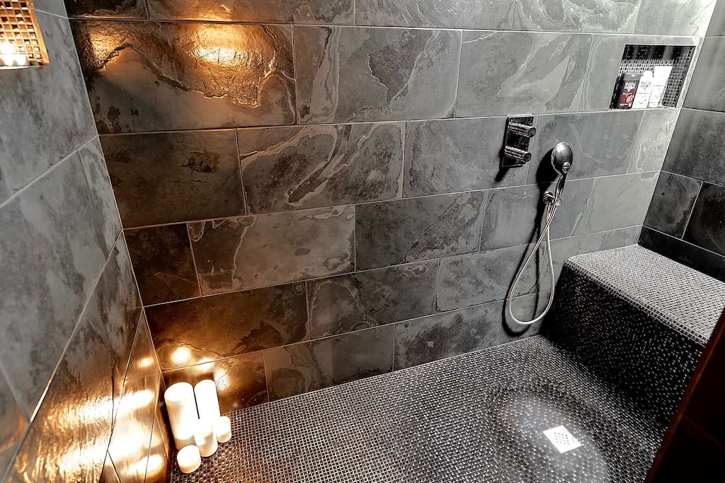 Natural stone shower for 2 with ceiling rain shower & cascade + 4 jet hand shower + very large seat for 2. The dark shower lit by candles is magical.... A sensory escape from the world.