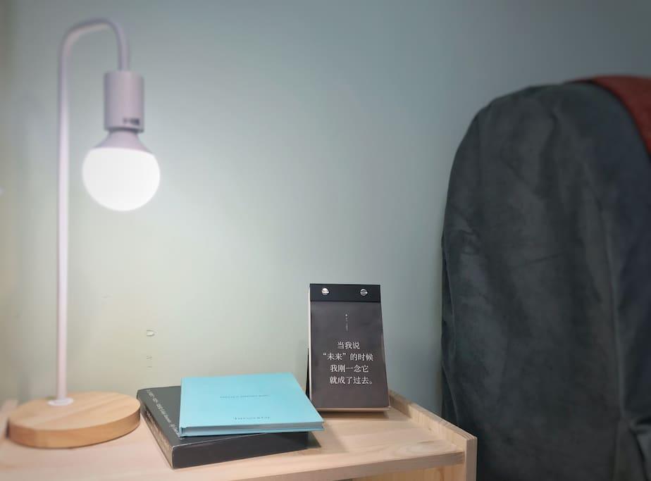 主卧的床头柜,有温暖的灯光和书籍