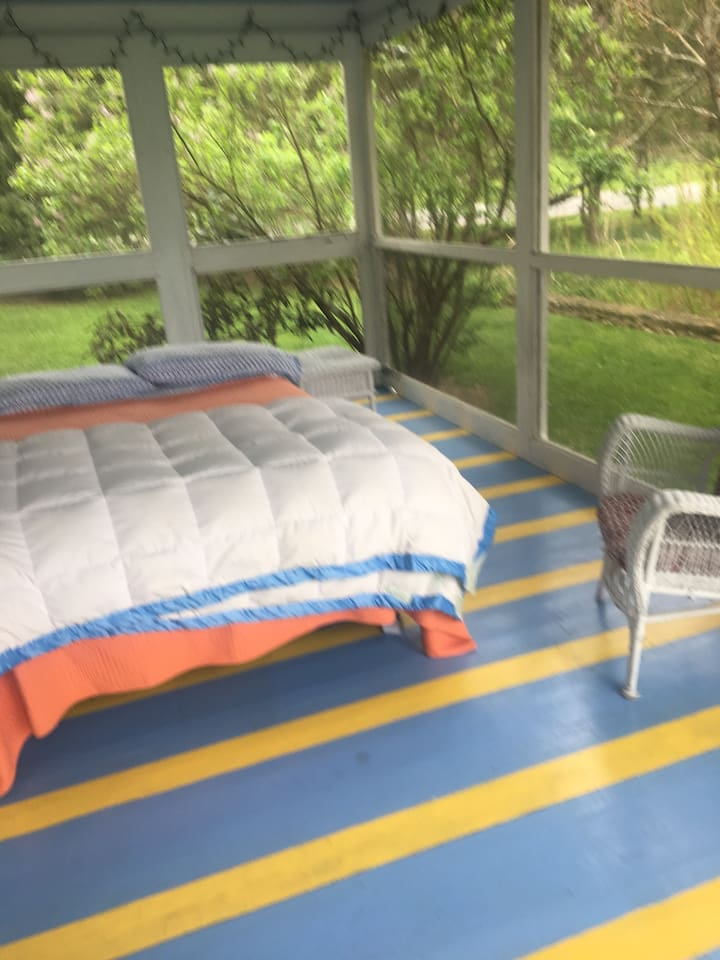 Queen bed out on cozy porch.