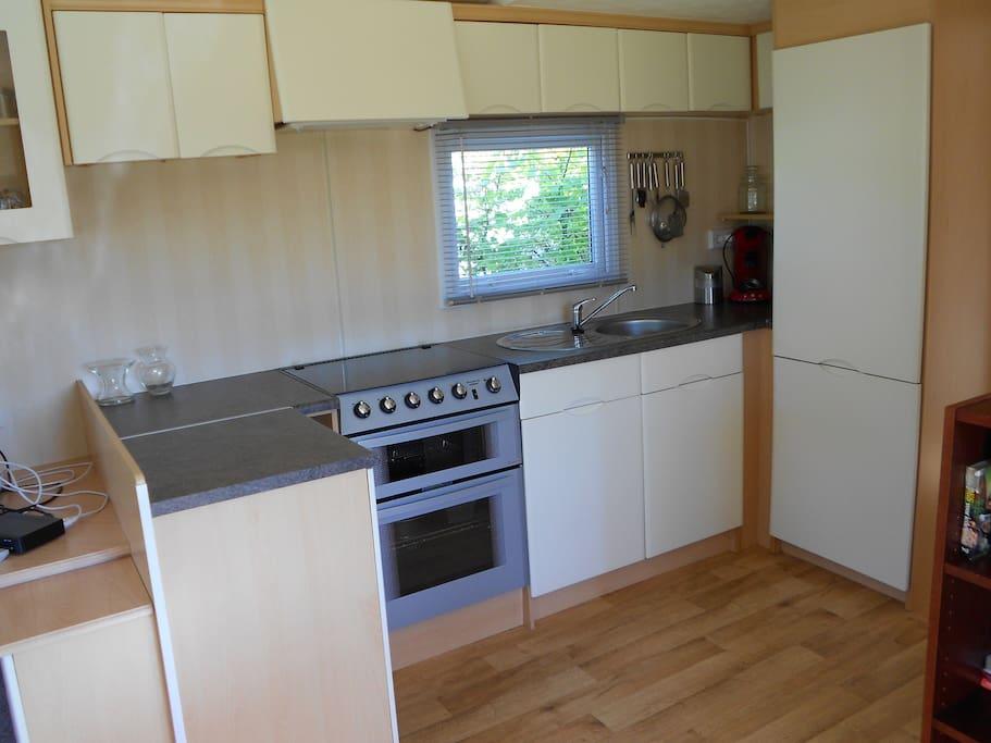Ruime keuken met koel-vriescombinatie, oven en grill.