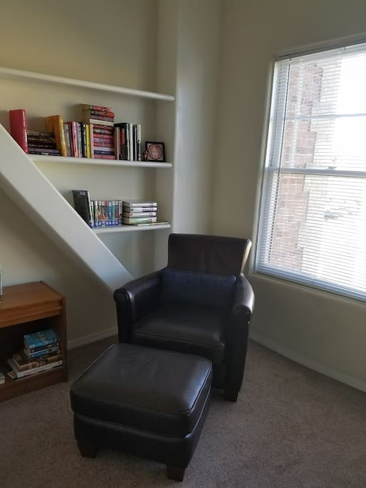 There is a comfortable leather reading chair and ottoman by the window for a quiet evening in!