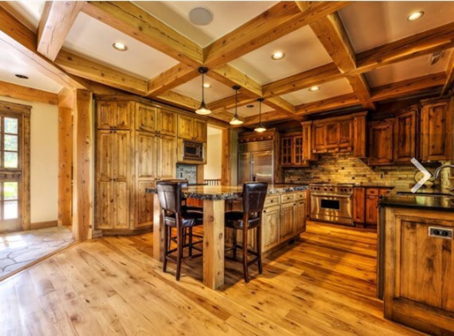 Gourmet Kitchen with Thick Slab Granite Center Island and Designer Appliances