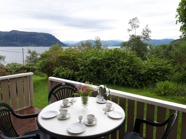 Covered terrace with round table, chairs and view to the Vanylvsfjord
