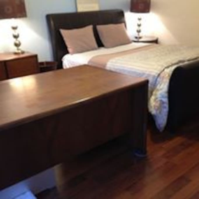 Queen size bed and large executive desk on second floor overlooking the pool
