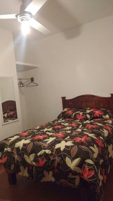 Dormitorio con cama matrimonial, espacio para colgar ropa, cajonera y ventilador de techo.