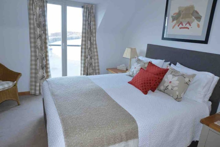 First floor bedroom with king-size bed. There is a Juliet balcony which overlooks the sea and harbour. This bedroom has an ensuite shower room and a spacious walk in wardrobe which is good for storing luggage.