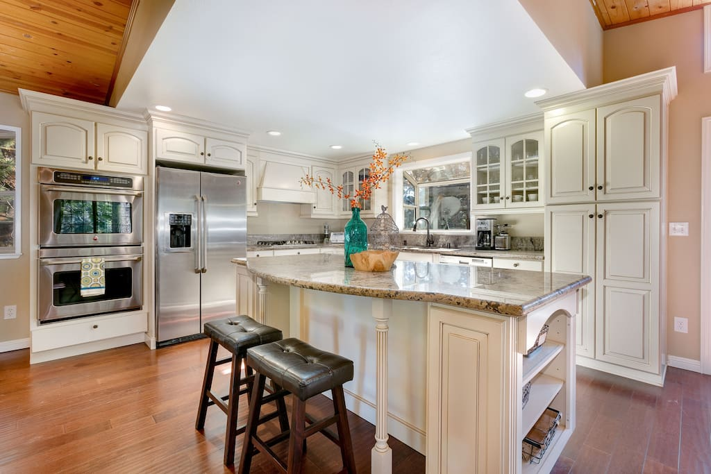 The gourmet kitchen features a large center island and double ovens.