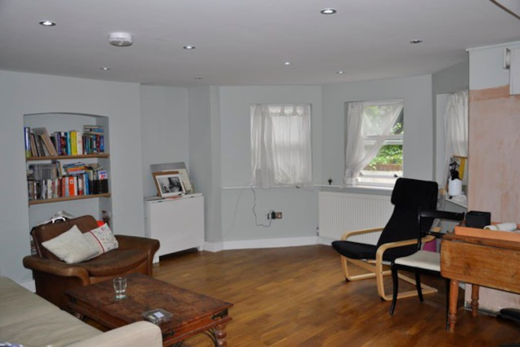 Other view of front room with working desk in the back