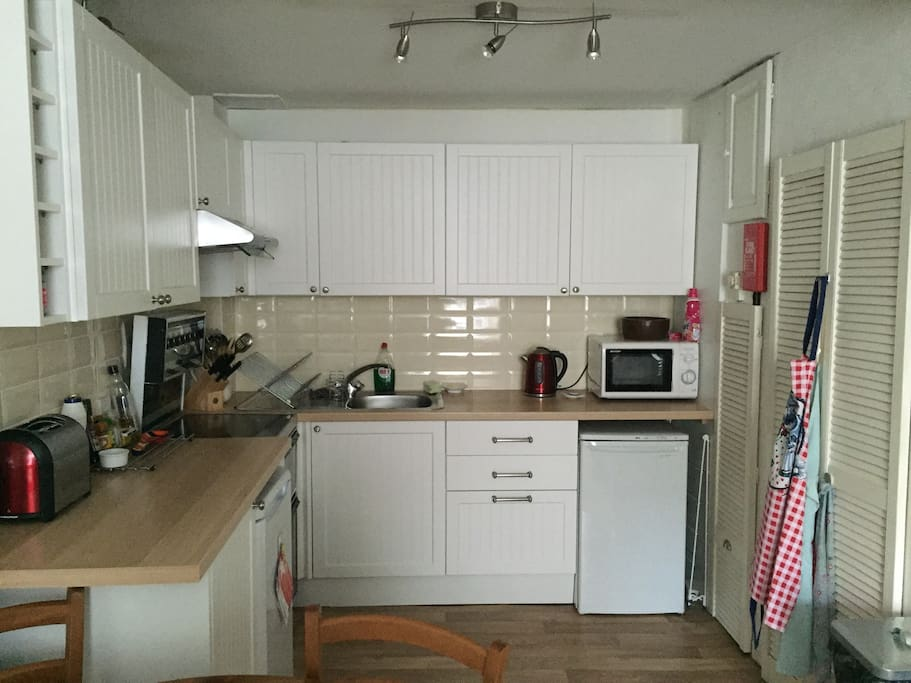 Kitchen with oven, microwave, toaster, kettle, fridge & freezer.