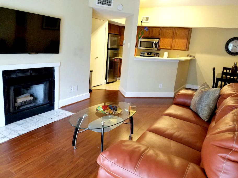 Living area has a dining room table, large sofa, mounted SMART TV and fireplace. The sofa pulls out to a full size bed with a Serta mattress, very comfortable for extra guests