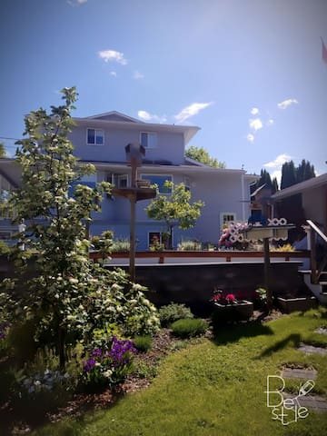 home with lower level suite and view of boardwalk leading to garden and gazebo