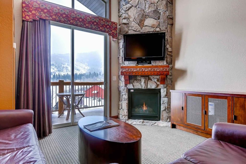 """Large living and family room features a floor to ceiling stone fireplace, 42"""" HDTV and sleeper sofa."""