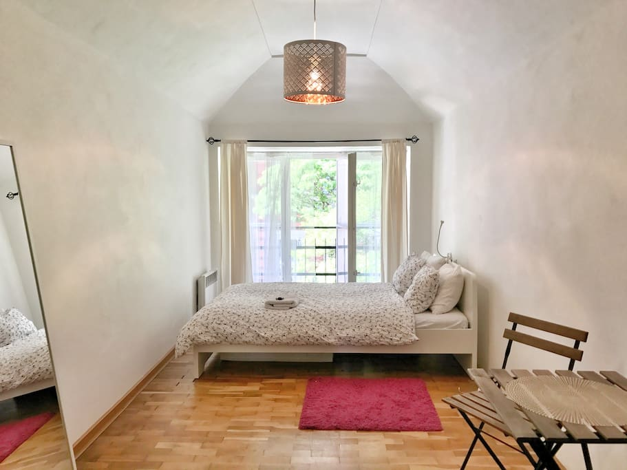 Bedroom with a French window into the street.