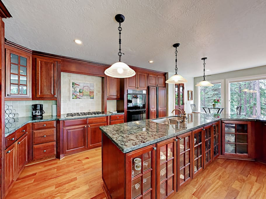 The gourmet kitchen features dark cherry cabinets, granite countertops, and high-end appliances.