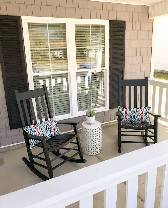 The front porch has four rocking chairs.