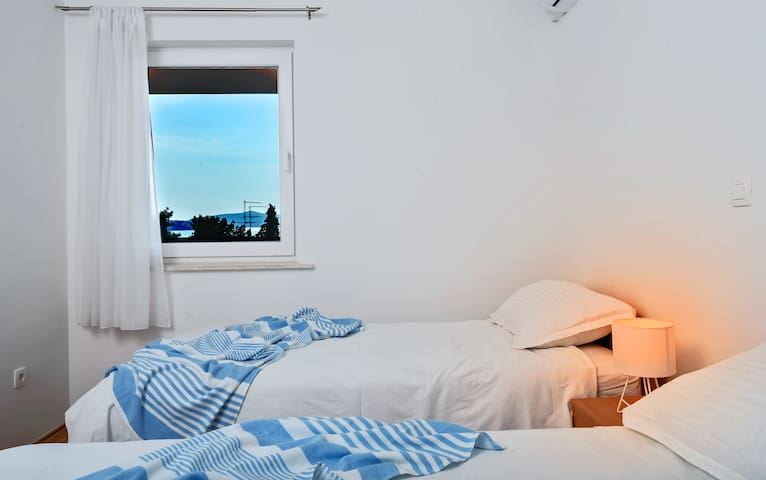 Smaller bedroom with seaview. These two beds can be joined well together to make a king size bed 180x200.