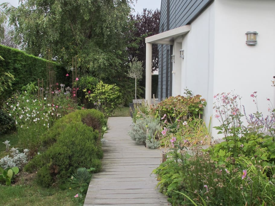 Jardin agréable, fleuri avec 2 terrasses.