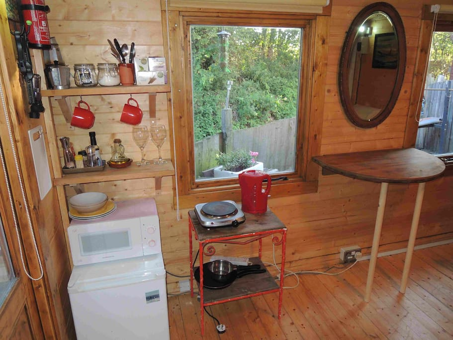 Mini fridge, microwave, kettle, toaster, coffee maker and hotplate for preparing a light meal. There's also a fold down table to prepare food on
