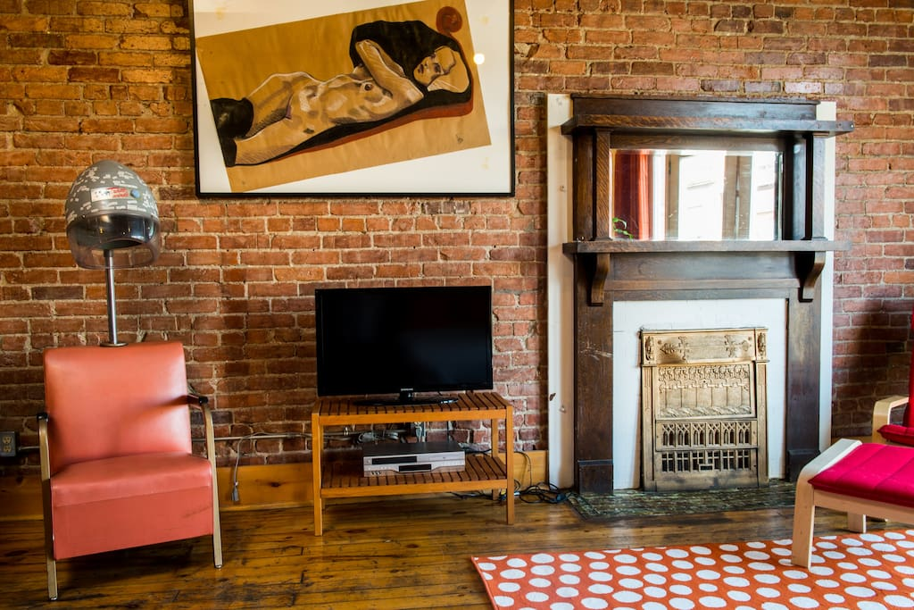 Vintage hair dryer seat, tv and old fireplace.