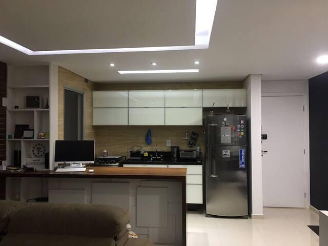 Cozinha americana aberta com a sala. As luzes podem variar de cor no teto.