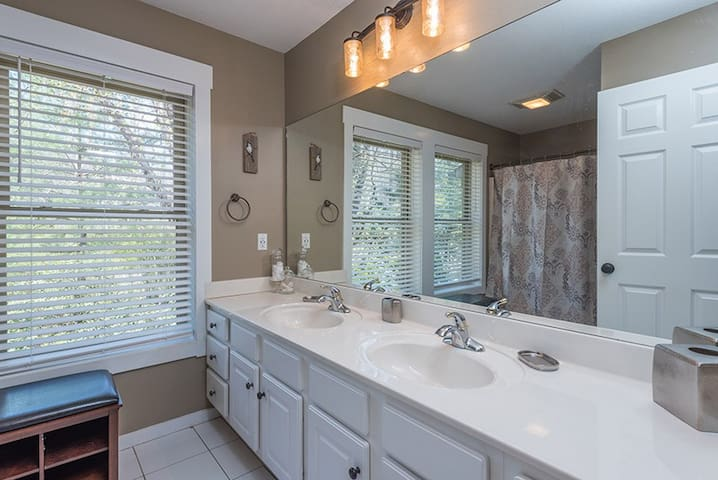 Hall bath with double vanity and shower/tub combination.