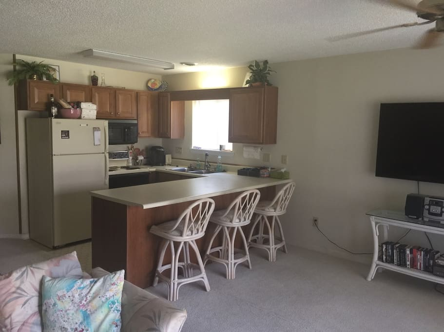Kitchen amenities include: refrigerator, freezer, Keurig coffee maker, microwave, toaster over, stove top, oven, double sink, counter top breakfast bar, and 3 stools.
