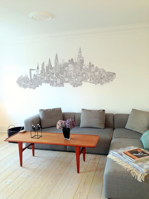 Cosy large living room with personal mural painting and authentic Danish teak coffee table