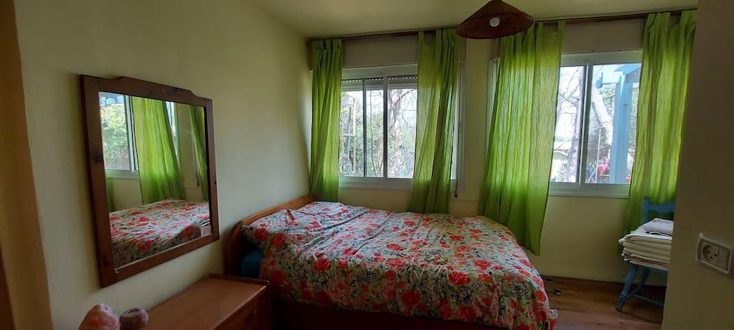 חדר שינה הורים עם חלונות גדולים לגינה