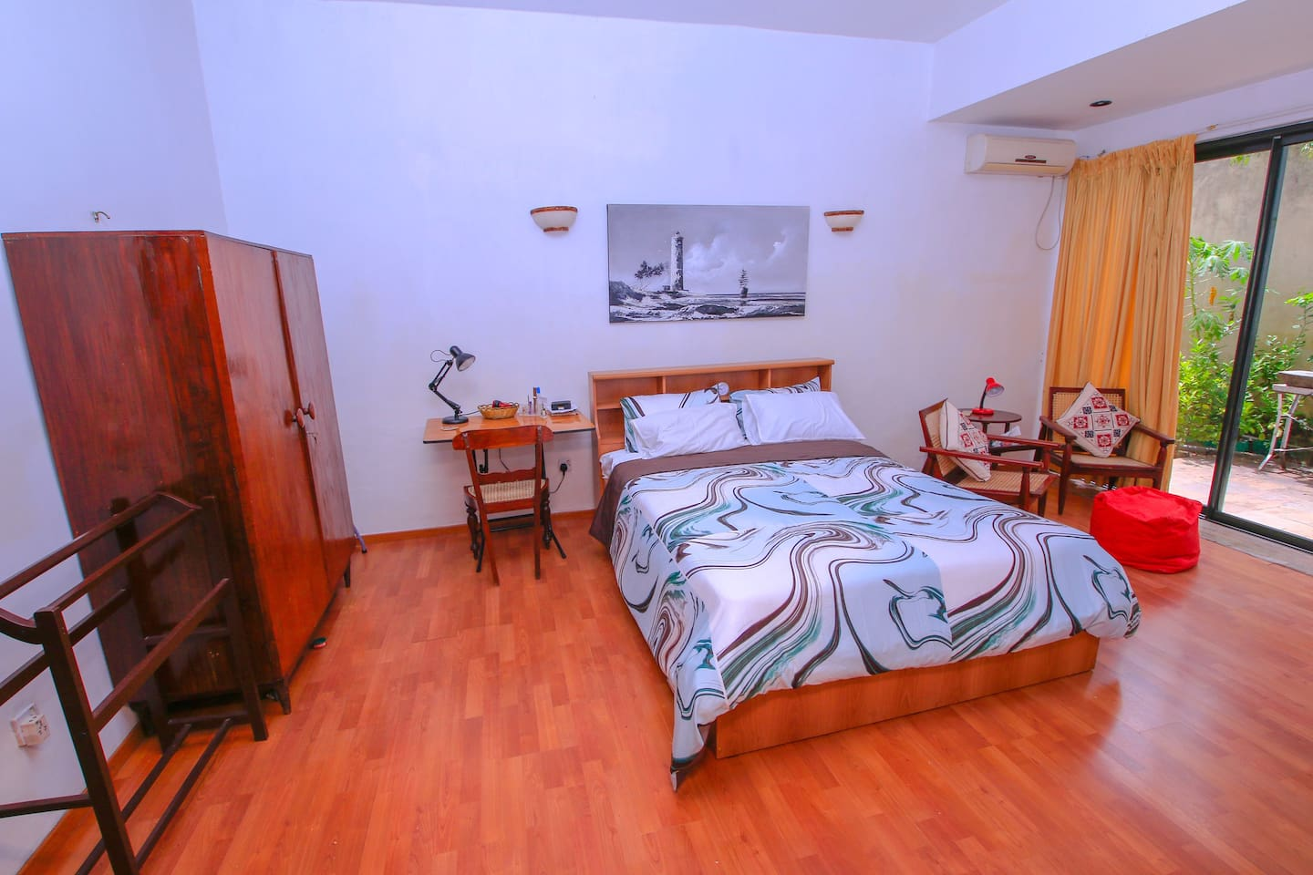 Cozy and spacious bedroom with queen-sized bed and work space, open to a homely garden area. A foldable single bed can be provided on request.