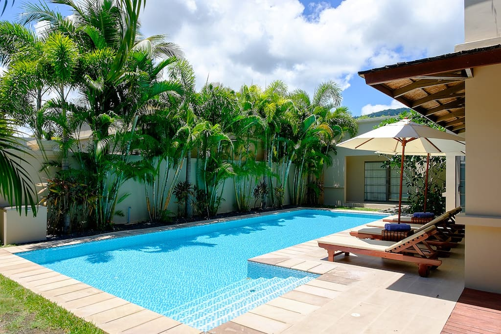 Your private pool with sunbeds in lush tropical garden