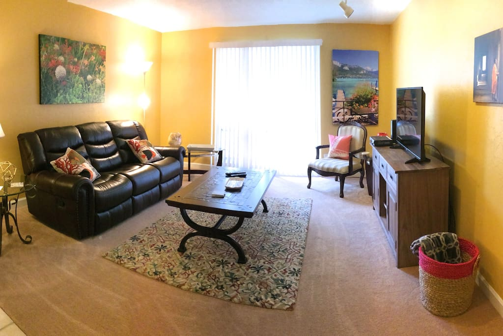 Living area with large screen TV, reclining leather sofa, wifi, cable