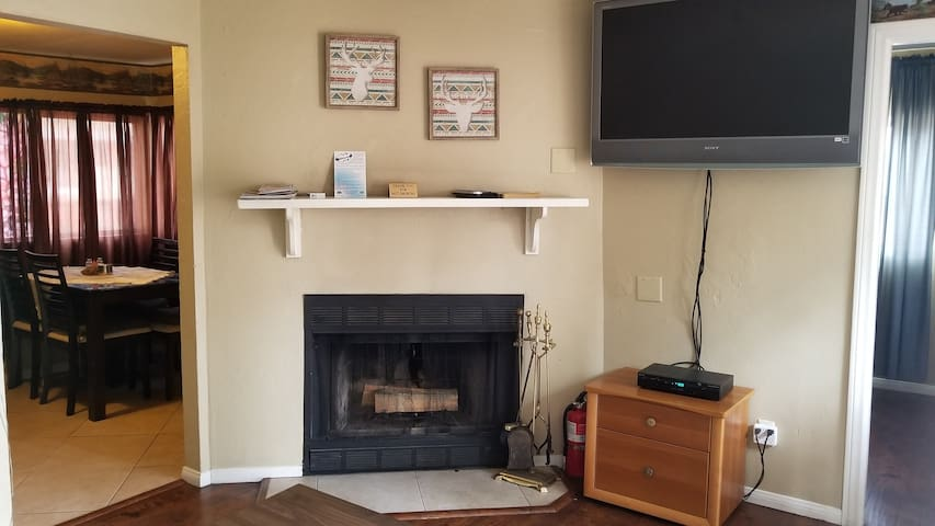 Living room with fireplace and large screen TV with Spectrum basic cable channels and Roku TV. HDMI for your external devices like DVD player or games console.