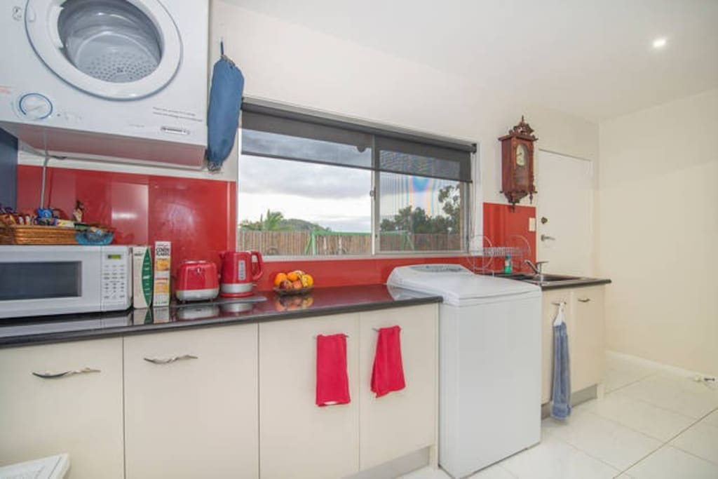Kitchenette with single hot plate, electric frying pan, rice cooker, microwave, jug and toaster plus plates in the cupboards,and laundry area, access to back yard which has table and chairs. The door here  separates your rooms from our house for your privacy.