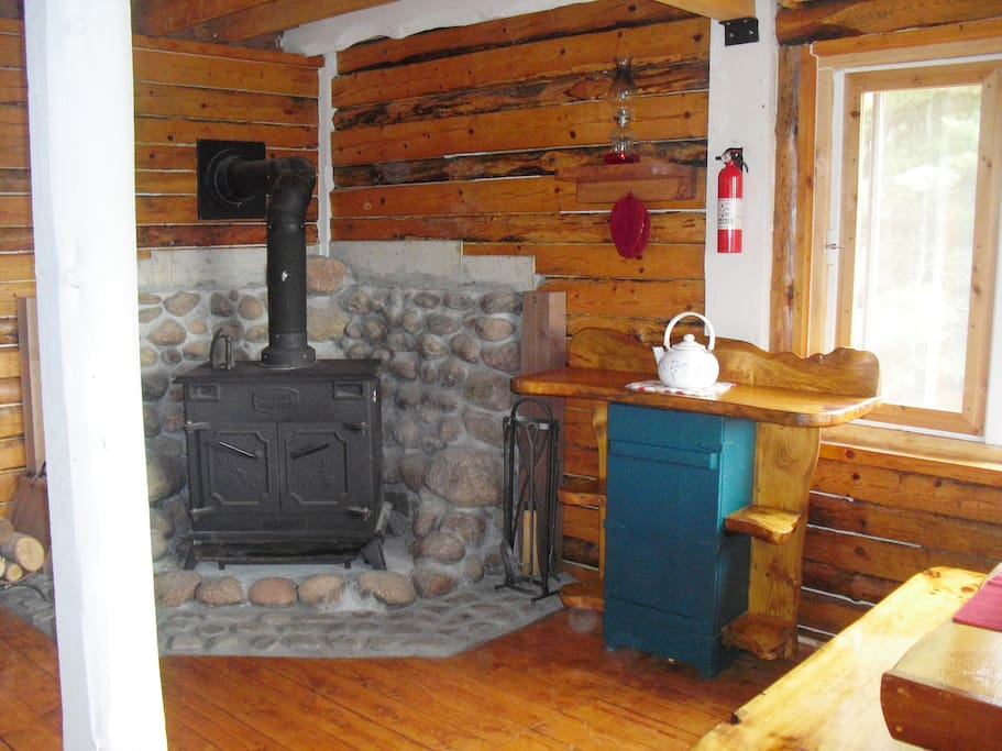 The woodstove's doors open to allow a screen to be put in to watch the fire.