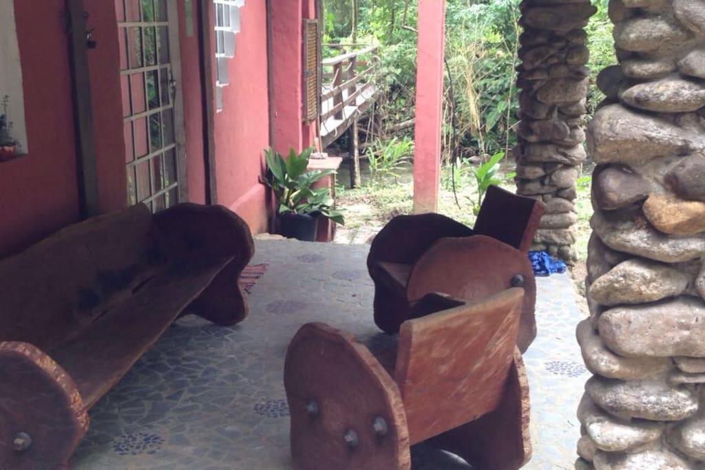 Área comum, varanda com bancos rústicos de madeira.