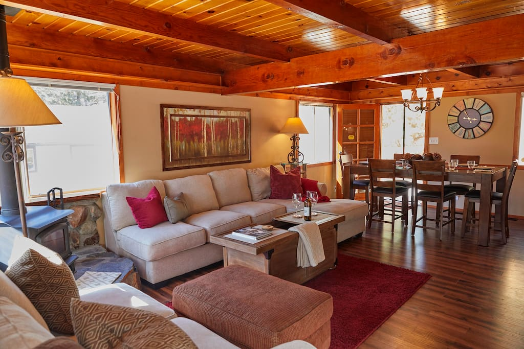 "Please meet our cozy Home!  This is the main level comfortable family room, just off the kitchen and dining area with a 60"" television.  This is where you'll enter the home from the front door and deck.  Comfortable seating area, views of our beautiful trees.  :)"