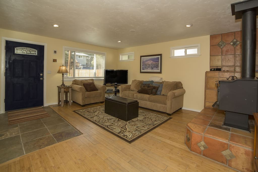 Open living room with bamboo wood flooring into a cozy living room with comfortable sofas, wood stove and a 47 inch flat screen lcd with a blu ray dvd player
