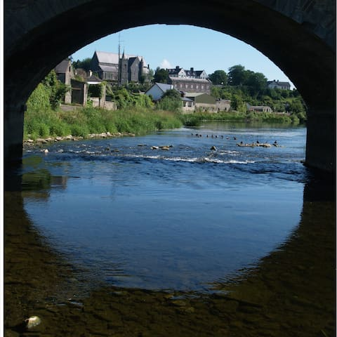 Thomastown Catholic Church through the eye of the bridge over river Nore.