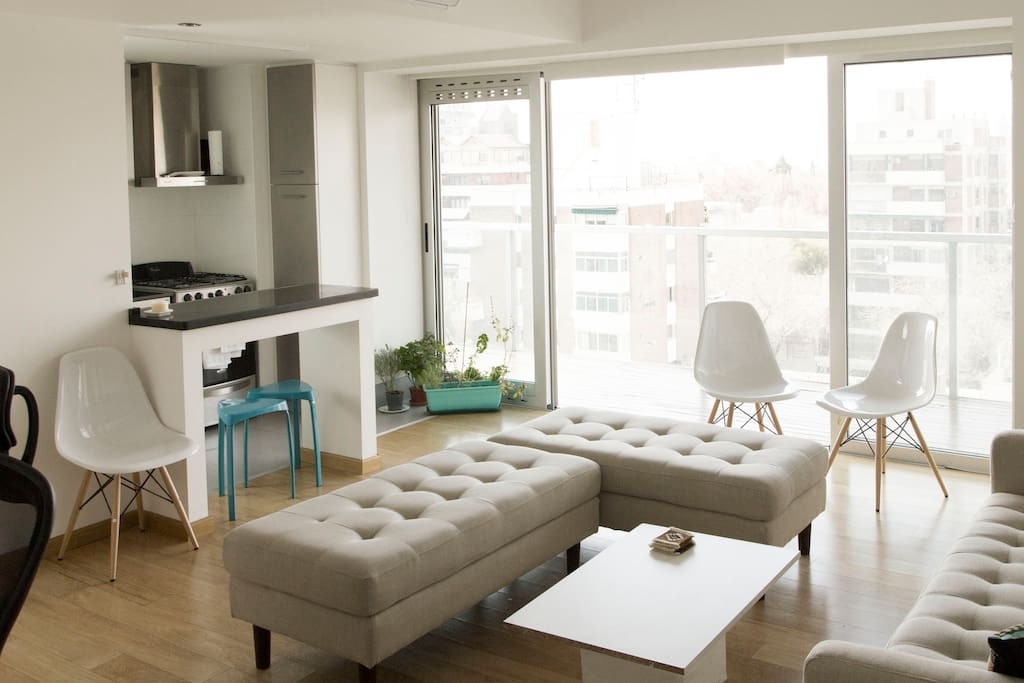 Living room with sliding glass doors, wraparound balcony and city views.