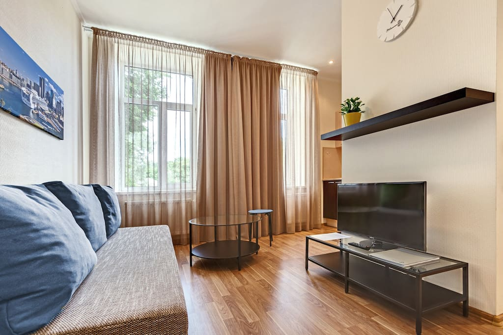 Living room has comfortable sofa and flat screen TV