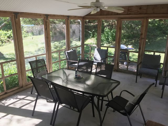 Screened in porch overlooks lush yard. Lounge in the hammock right outside!