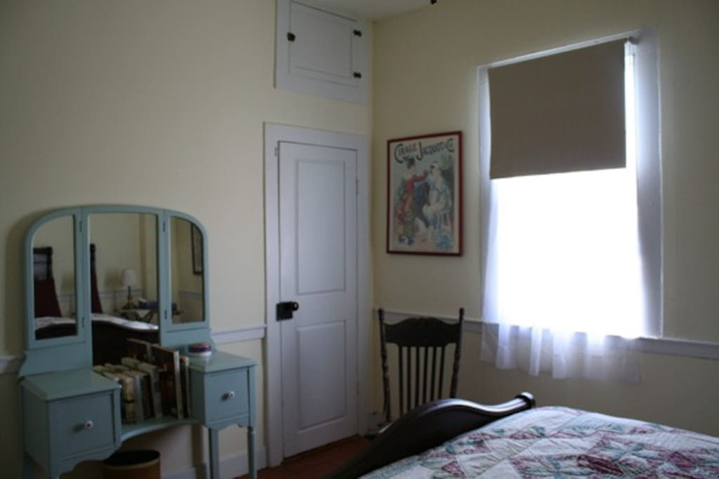Dressing table, closet door and south facing window with darkening shade