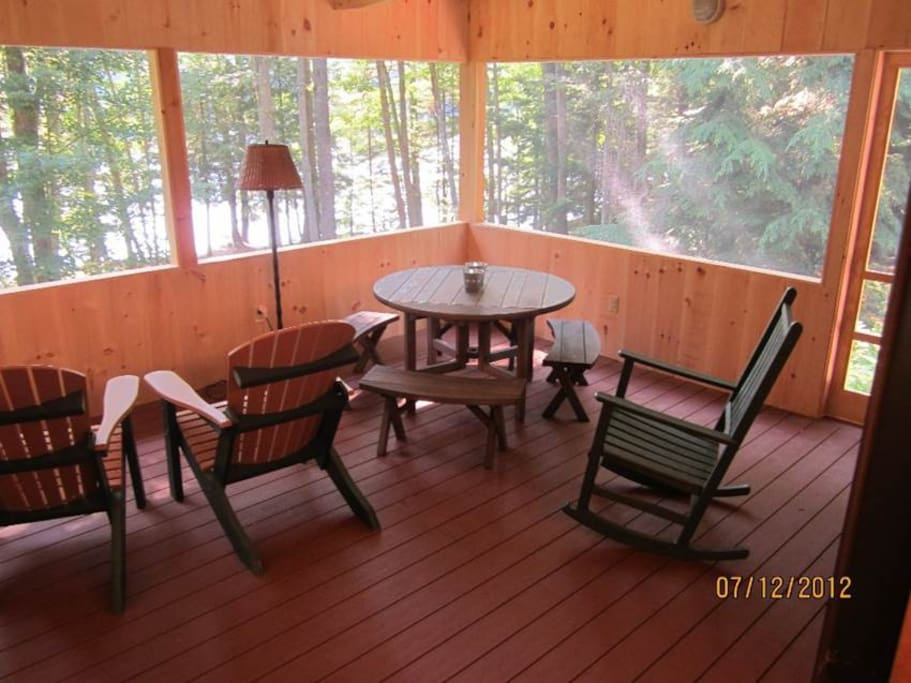 view from house onto right side of screened in porch.  picnic table for 4, two rockers, two adirondack chairs,