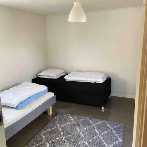Soveværelse med to enkeltsenge og udgang til egen terrasse/have