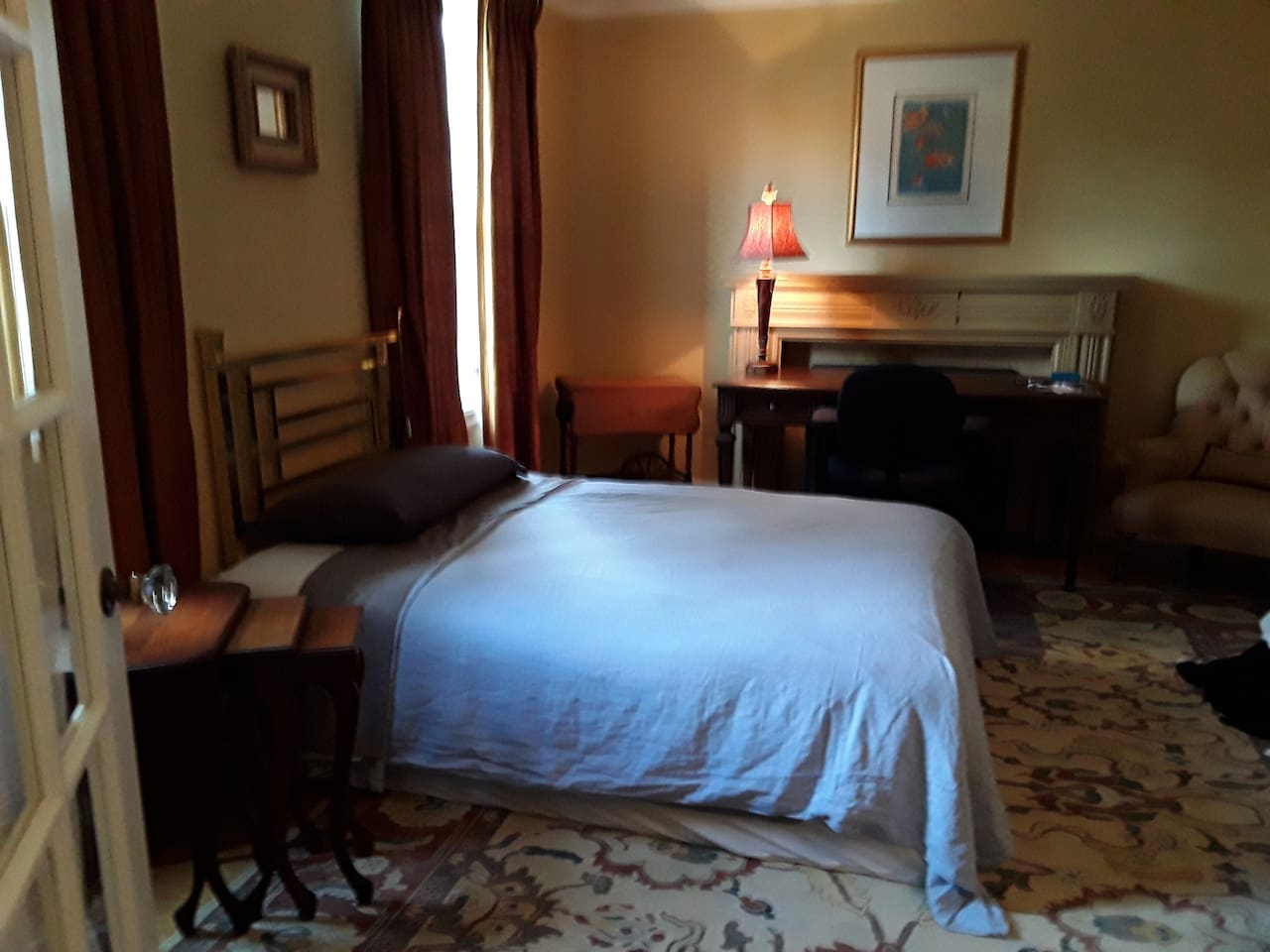 Large spacious room with queen bed, and large working desk.  Window opens for cool breeze on warm days.  Comfortable sitting chairs for breaks or meetings.  No stairs to climb to access half bathroom. Shared shower upstairs. Enjoy the gardens.