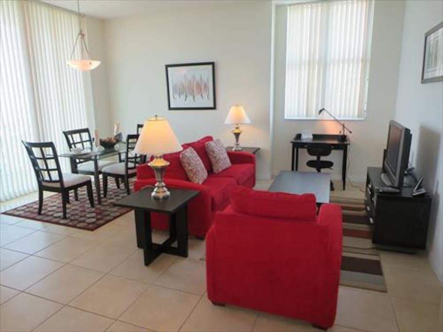 Spacious living room with seating area, dining area, entertainment center and convenient work desk