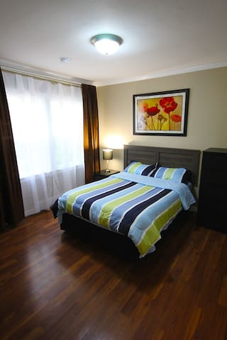 """This room (double size bed) has a closet area to the right and also includes a wall mounted 42"""" LED flatscreen TV with Netflix and a Roku Streaming Box. The large window overlooks the front yard and provides lots of natural light."""