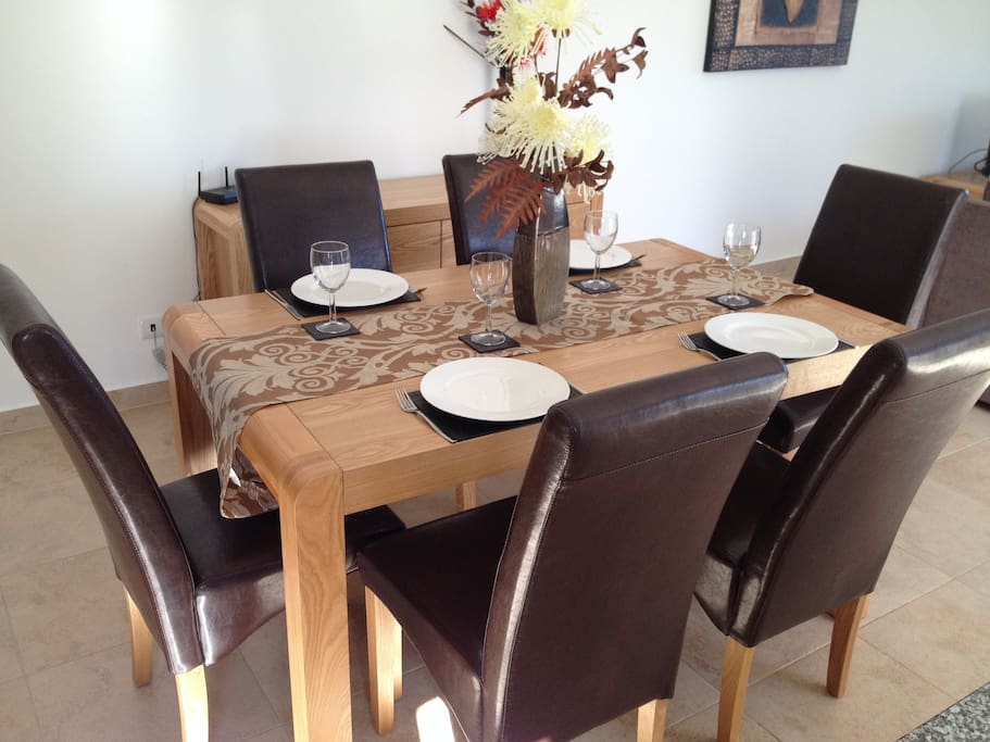 Dine at this luxurious table with leather chairs.