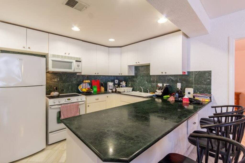 The full equipped kitchen has granite counters and a breakfast bar
