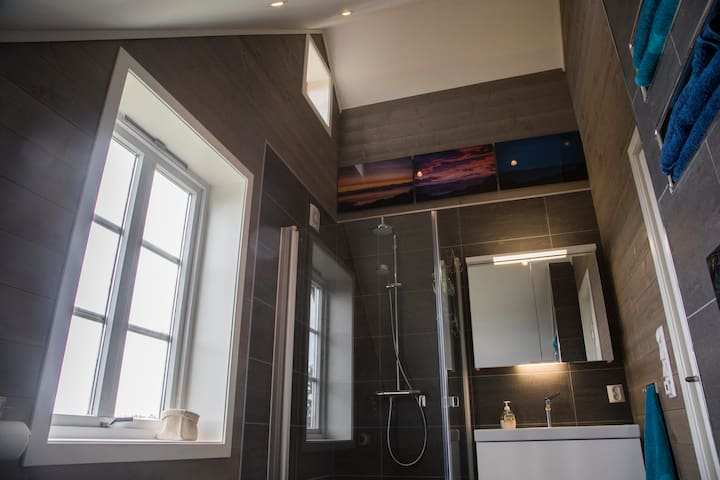"""The bathroom was completely renovated and extended in 2016. It includes parts of the loft and is decorated with photos of the magnificent view you will have when doing your """"business"""" :)"""